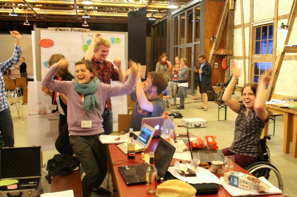Sechs Bootcamper*innen heben freudestrahlend die Hände in die Luft. Hinter ihnen liegen anstrengende Stunden des Planspiels während des Campaign Bootcamps 2014. Zu sehen sind junge Frauen und Männer, darunter eine Rollstuhlfahrerin.