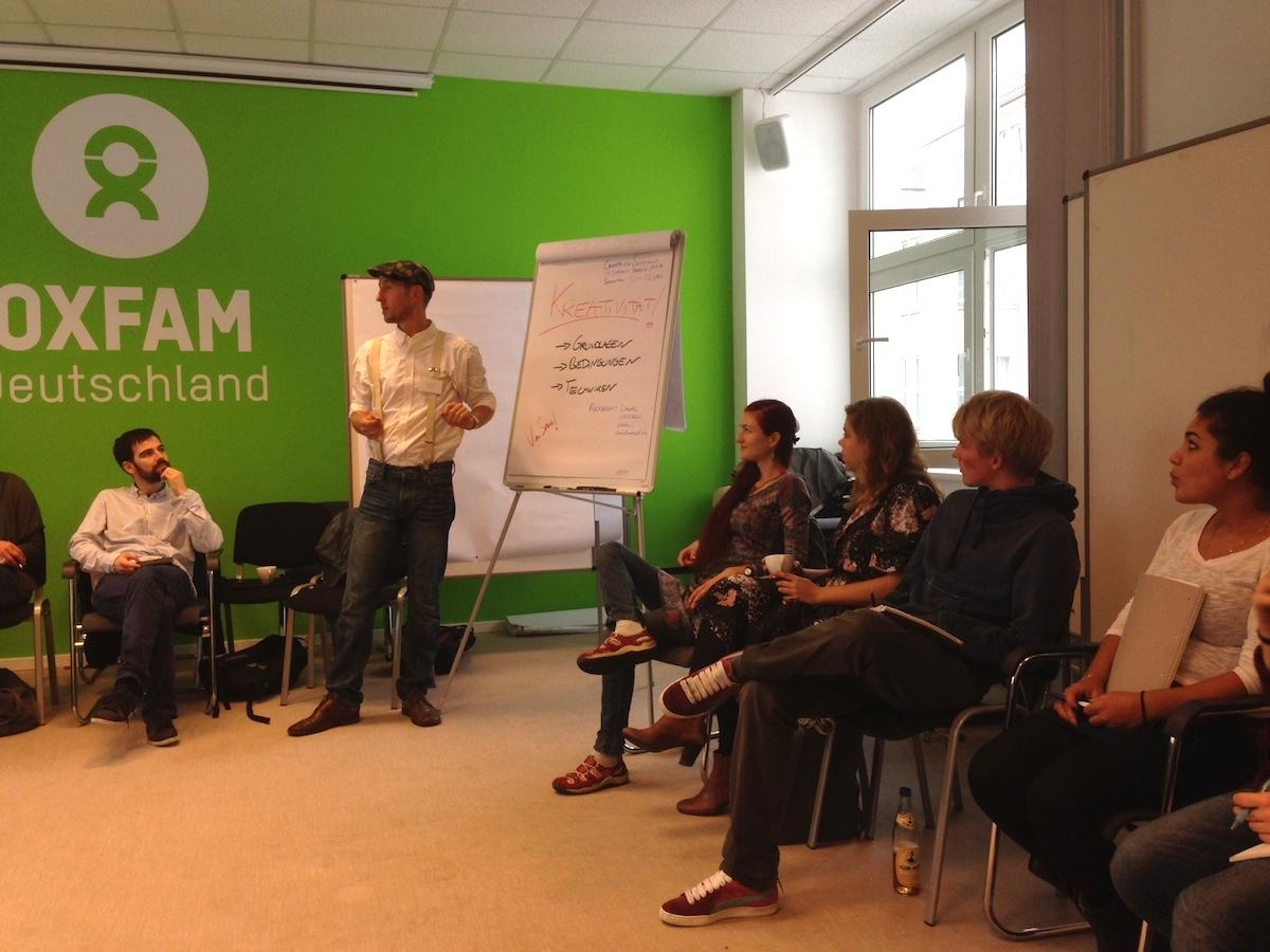 Daniel Unsöld kennt viele Kreativitätstechniken und teilt sein Wissen mit einer Gruppe von Boostcamper*innen. Im Hintergrund an der Wand ist das Logo von Oxfam Deutschland zu sehen.