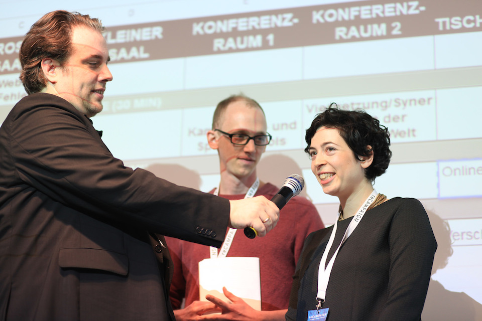 Anne Isakowitsch vom Campaign Boostcamp Deutschland wird auf der Bühne der recampaign interviewt. Sie trägt einen schwarzen Pullover und das weiße Ticket-Band der recampaign um den Hals.