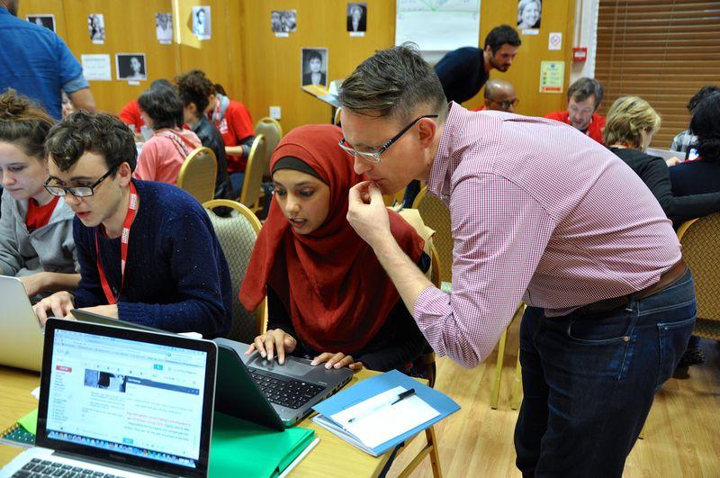 Eine Teilnehmerin mit rotem Kopftuch und ein Trainer mit rosa Hemd arbeiten gemeinsam an einer Aufgabe am Laptop. Es ist eine Situation im Campaign Bootcamp in Großbritannien, wo das Bootcamp bereits drei Mal stattgefunden hat.